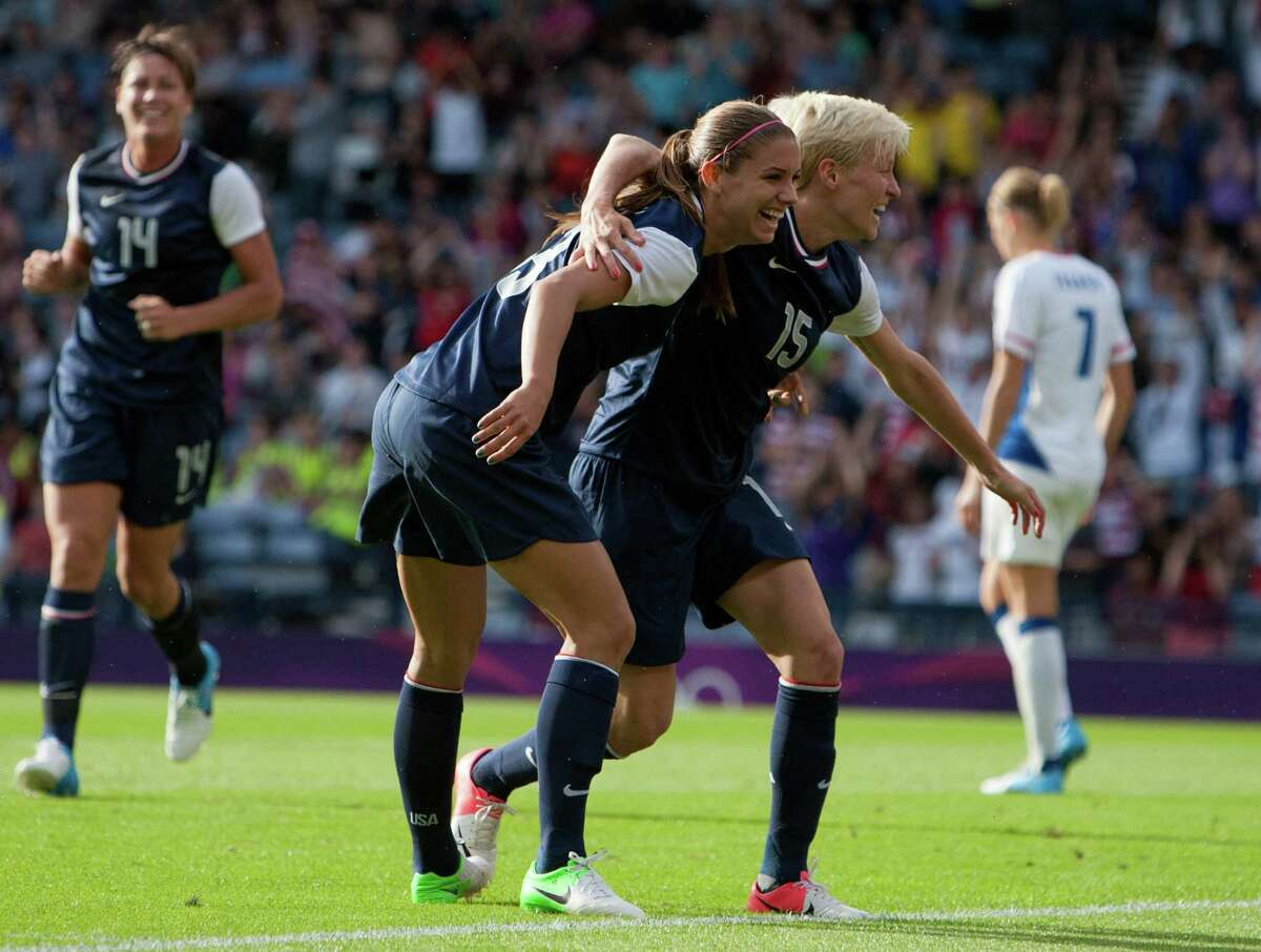 United States' Megan Rapinoe, right, Alex Morgan, center, celebrate together after Morgan scores her second goal during the women's group G soccer match between the United States and France at the London 2012 Summer Olympics, Wednesday, July 25, 2012, at Hampden Park Stadium in Glasgow, Scotland. (AP Photo/Chris Clark)