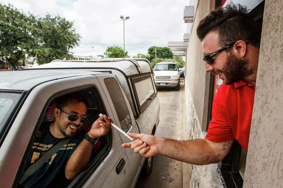 The Texans' Connor Barwin, right, provides a straw and service with a smile to Marvin Santamaria while working the drive-thru at a McDonald's as part of the Back to Football Caravan. Photo: Michael Paulsen / © 2012 Houston Chronicle