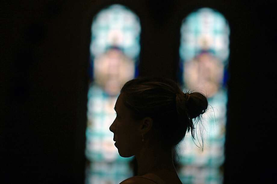 A woman is framed near stained glass windows during Mass Of The Anointing Of The Sick  held on Wednesday, July 25, 2012 at Saint Ann's Basilica in West Scranton, Pa.,, during the annual Solemn Novena in honor of St. Ann. (AP Photo/The Scranton Times-Tribune, Butch Comegys) Photo: Butch Comegys, Associated Press