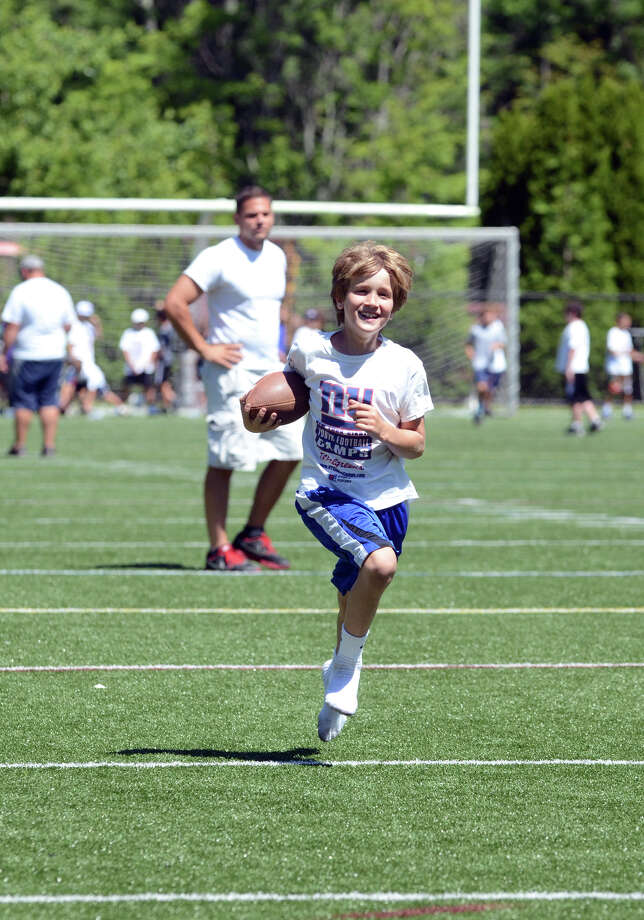 Christian Alliegro, 8, of Darien, participates in a relay race during the New York Giants football youth camp at St. Lukeís High School in New Canaan on Wednesday, July 25, 2012. Photo: Amy Mortensen / Connecticut Post Freelance