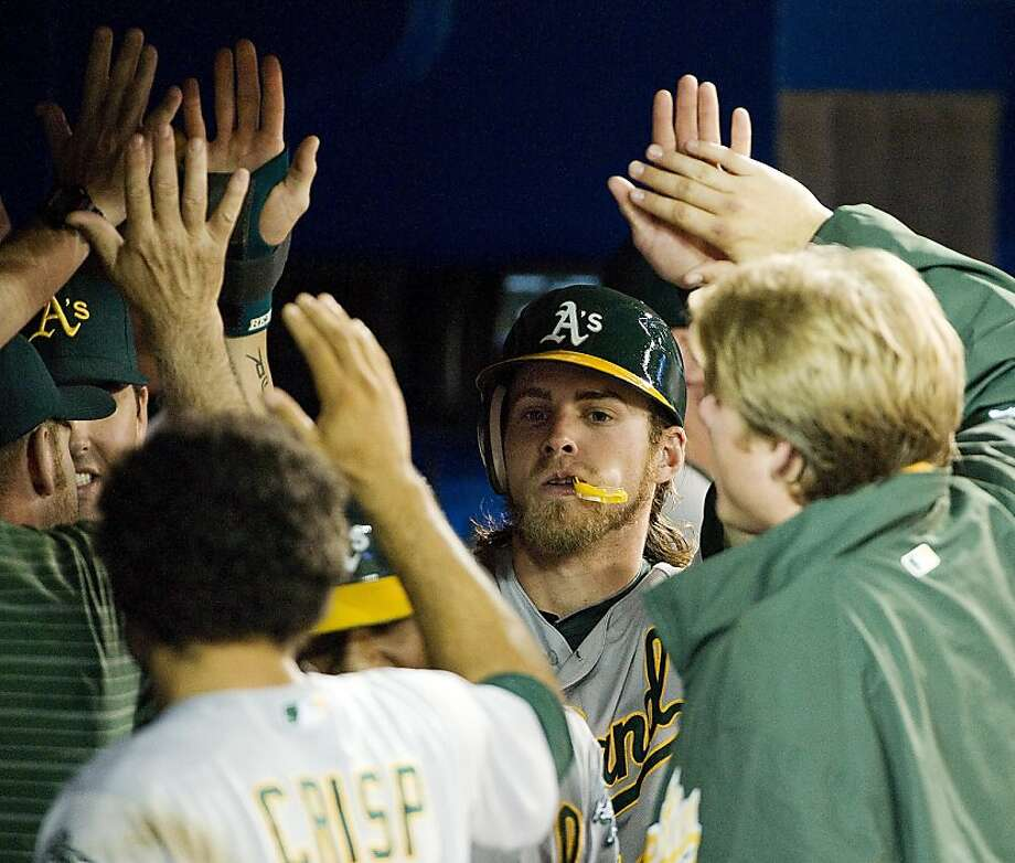 Oakland Athletics' Josh Reddick, center, celebrates in the dugout with teammates after scoring on an RBI double by Brandon Inge the during second inning of a baseball game against the Toronto Blue Jays in Toronto on Wednesday, July 25, 2012. (AP Photo/The Canadian Press, Aaron Vincent Elkaim) Photo: Aaron Vincent Elkaim, Associated Press