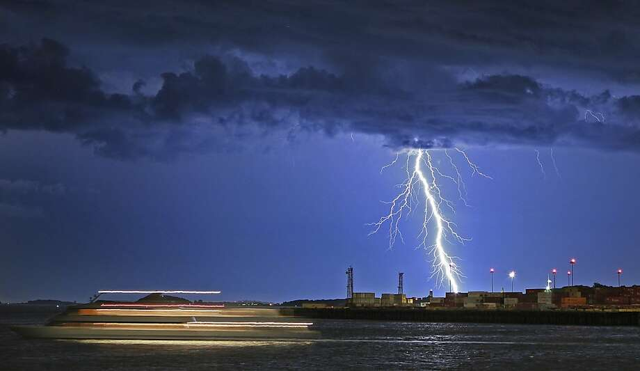 In this Tuesday, July 24, 2012 time exposure photo, lightning strikes as a ship passes on an evening cruise in Boston Harbor.  (AP Photo/Boston Herald, Matthew West)    BOSTON GLOBE OUT. METRO BOSTON OUT. MAGS OUT. ONLINE OUT. Photo: Matthew West, Associated Press