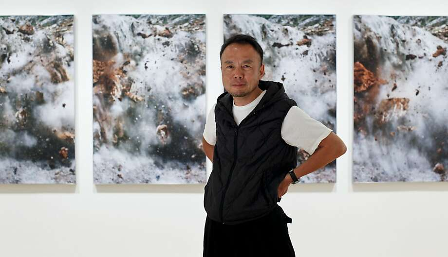 Photographer Naoya Hatakeyama, seen on Tuesday, July 24, 2012 in San Francisco, Calif. in front of images from his Blast series, will have his first show in the U.S. at SFMOMA. Photo: Russell Yip, The Chronicle