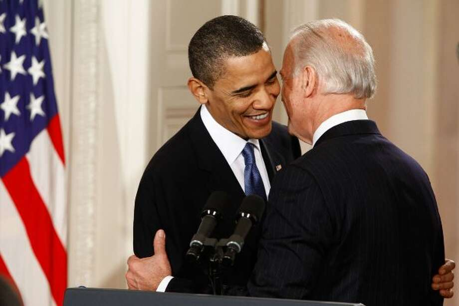 "President Obama is embraced by Vice President Joe Biden before signing the Affordable Health Care Act, a moment before the mike caught Biden telling his boss:  ""Mr. President, this is a big f****** deal."" (Chip Somodevilla / Getty Images)"