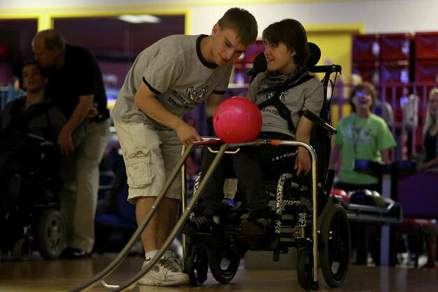 Adrian Pressey helps Kassie Sanchez bowl with the Special Olympics and their Clark High School teammates at University Bowl in San Antonio on Monday, May 14, 2012. Photo: Lisa Krantz, San Antonio Express-News / San Antonio Express-News