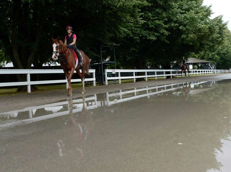 Exercise rider for Casse Racing Stables Erin Rock takes Rei, left out for his morning exercise in the rain at the Saratoga Race Course in Saratoga Springs, N.Y. July 26, 2012    (Skip Dickstein/Times Union) Photo: Skip Dickstein