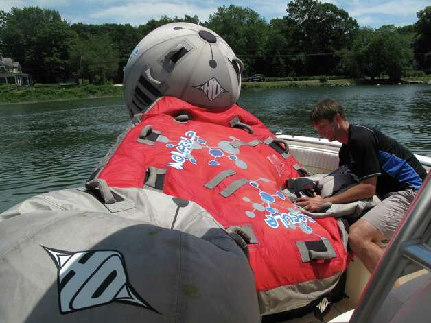 Jim Batson deflates his four-person tube after taking his three kids and wife out for a ride on Long Island Sound on a sunny summer morning, Friday, July 6, 2012. Darien, Conn. Photo: Thomas Michael