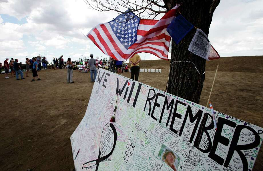 "An Aurora, Colo., sign says ""We Will Remember."" We do remember, but maybe only for a week. Photo: Ted S. Warren, Associated Press"