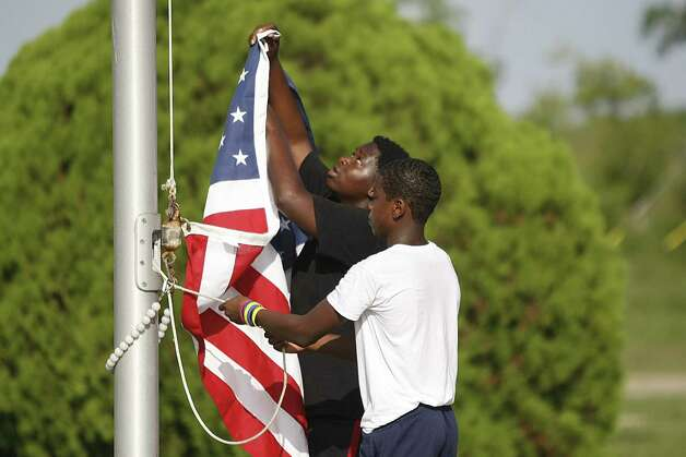 DeMarcus Anthony, 16, back, and Jacobi Faux, 12, raise the American flag at the Bessie Swindle Community Center. DeMarcus appreciates the responsibility and makes sure the flag never touches the ground and holds it up high. Photo: Nick De La Torre