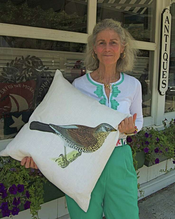 Minda Daniell displays a decorative throw pillow that will be among items in the Fairfield Women's Exchange's annual sidewwalki sale at its shop in Southport, Thursday through Saturday. The philanthropic group said sale merchandize would be marked down 25 percent to 50 percent. Photo: Contributed Photo / Fairfield Citizen contributed