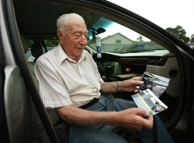 Frank Scaduto, 89 of Bridgeport, sits in his 1997 Cadillac while showing pictures of his passion, a 1936 Ford convertible coupe tha