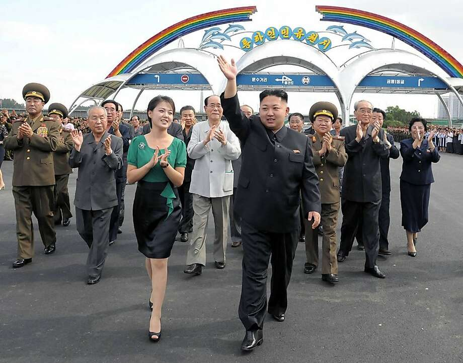 In this Wednesday, July 25, 2012 photo released by the Korean Central News Agency (KCNA) and distributed in Tokyo by the Korea News Service Thursday, July 26, 2012, North Korean leader Kim Jong Un, foreground right, accompanied by his wife Ri Sol Ju, foreground left, waves as they attend the completion ceremony of the Rungna People's Pleasure Ground in Pyongyang. (AP Photo/Korean Central News Agency via Korea News Service) JAPAN OUT UNTIL 14 DAYS AFTER THE DAY OF TRANSMISSION Photo: Associated Press