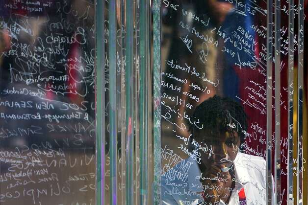 USA Chef De Mission Teresa Edwards, a five-time Olympian in women's basketball, puts her signature on the Olympic Truce Wall during a welcome ceremony for Team USA at the Olympic Village on the eve of the Opening Ceremonies for the 2012 London Olympics on Thursday, July 26, 2012. Photo: Smiley N. Pool, Houston Chronicle / © 2012  Houston Chronicle