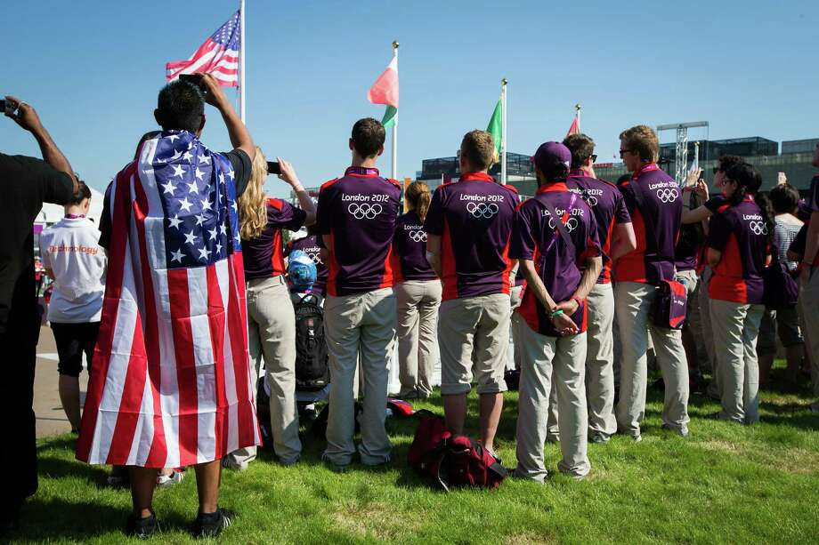Volunteers take photos as the American flag is raised during a welcome ceremony for Team USA at the Olympic Village on the eve of the Opening Ceremonies for the 2012 London Olympics on Thursday, July 26, 2012. Photo: Smiley N. Pool, Houston Chronicle / © 2012  Houston Chronicle