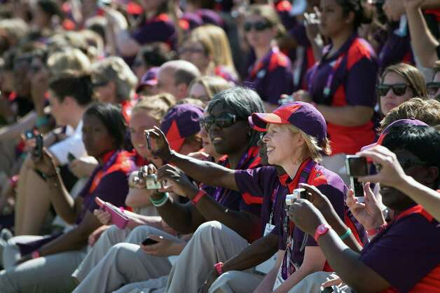 Volunteers take photos during a welcome ceremony for Team USA at the Olympic Village on the eve of the Opening Ceremonies for the 2012 London Olympics on Thursday, July 26, 2012. Photo: Smiley N. Pool, Houston Chronicle / © 2012  Houston Chronicle