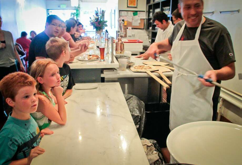 Kids watch Russell Stein cook pizzas in the wood burning oven (Special to the Chronicle)
