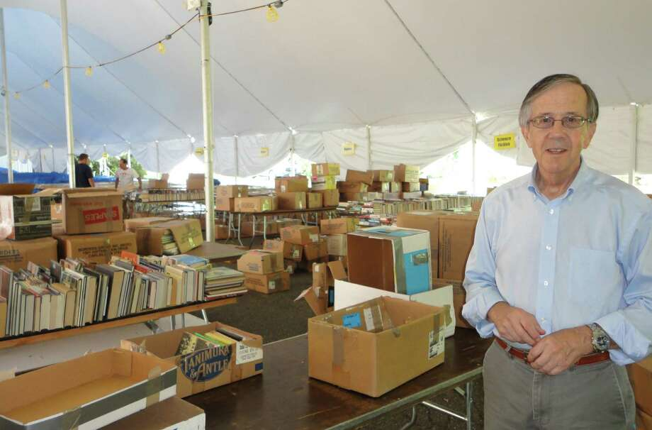 Pequot Library Executive Director Dan Snydacker poses in the largest of the tents set up on the library lawn for this year's summer book sale, which opens Friday. He will step down as executive director at the end of July shortly after the conclusion of this year's sale. Photo: Meg Barone / Fairfield Citizen freelance
