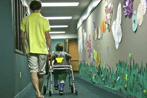 Reis Wohlfahrt heads down the hall with buddy Willem Center. This is Reis' first year attending Super Place Camp.