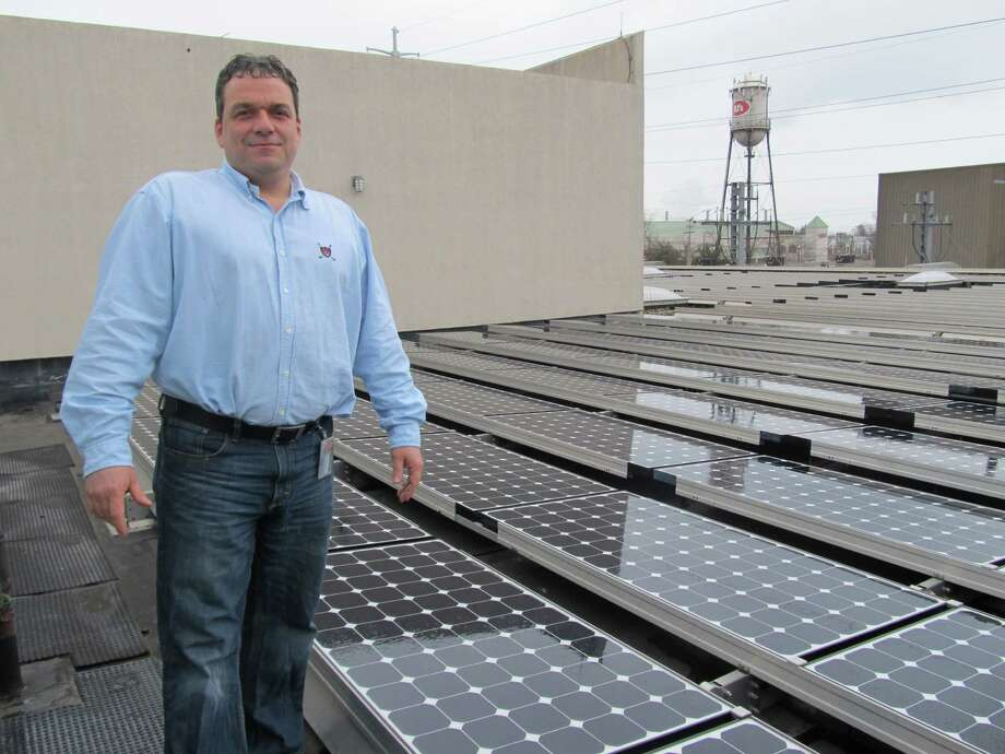 Jim Gildea, Bigelow Tea Co.'s plant manager, in April 2011 stands amidst 900 solar panels that the company installed on the roof of its Fairfield headquarters in 2005 to produce 10 percent of its energy. Fairfield and Westport are among four towns chosen to participate in  Solarize Connecticut, a state program that lowers the cost of residential solar panel installations through group purchasing. Photo: File Photo, ST