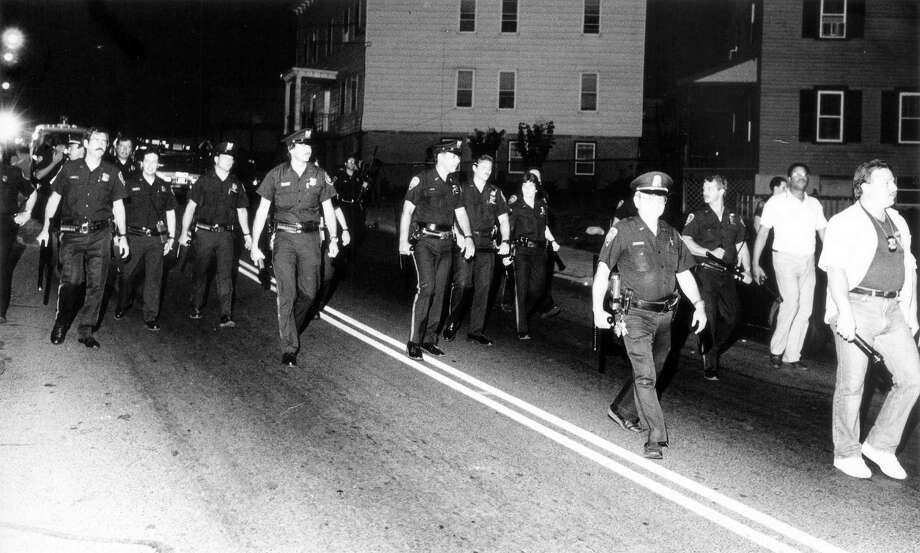 July 30, 1987: A line of police officers walk along West Main Street as they cleared the area of rowdy youths after a rap concert at the Yerwood Center ended in stabbings and a melee ensued outside. Photo: File Photo