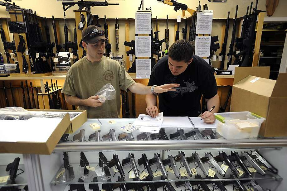As new guns arrive and are unpacked, employees Aaron Grant(L) and  Steve Eichhorn enter the weapons serial numbers in to a log book at Gun Vault in Mountain View, CA July 25th, 2012. Photo: Michael Short, Special To The Chronicle