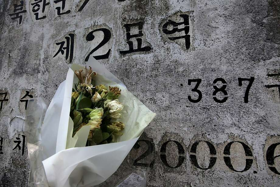 """In this Thursday, June 28, 2012 photo, wilted flowers sit in front of a headstone at the """"enemy cemetery,"""" where hundreds of Chinese and North Korean soldiers who died in the Korean War are buried, just south of the Demilitarized Zone in Paju,  South Korea. (AP Photo/Hye Soo Nah) Photo: Hye Soo Nah, Associated Press"""
