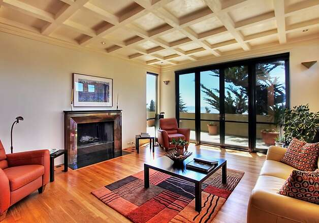 A fireplace, coffered ceilings and wall of windows with doors opening to the extended patio are among highlights of the living room. Photo: Todd Foster, The Tour Factory
