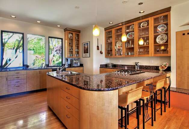 Glass-front cabinetry, hardwood flooring and marble countertops are among the elegant details of the spacious island kitchen. Photo: Todd Foster, The Tour Factory