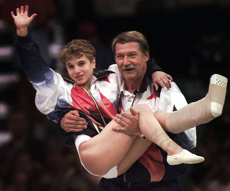 USA's Kerri Strug is carried by her coach Bela Karolyi as she waves to the crowd on her way to receiving her gold medal in 1996. What feats will this year's games bring? Photo: File Photo, Associated Press / AP