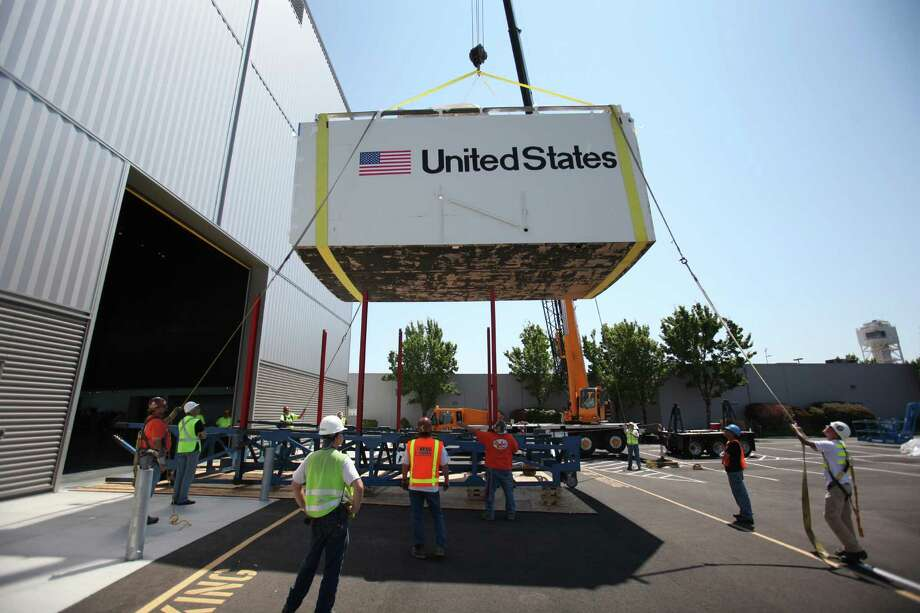 The aft section of the Space Shuttle Trainer payload bay is lowered onto its support during delivery to the Museum of Flight on Thursday, July 26, 2012. The crew cabin was delivered earlier to the museum aboard NASA's Super Guppy. The middle section of the Shuttle trainer is scheduled to be delivered on August 9th. Photo: JOSHUA TRUJILLO / SEATTLEPI.COM
