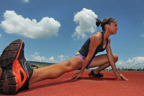 Alexus Henry, 14, stretches before practicing the high jump on Wednesday. The Bridge City athlete will compete in the 2011 USATF Junior Olympic Track and Field Championships in late July.  Guiseppe Barranco/The Enterprise