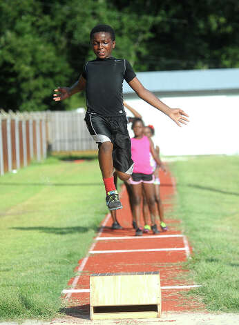 Port Arthur track club's Talel Malik practices his long jump at the Port Arthur auxillary track in Port Arthur, Tuesday, July 3, 2012. Tammy McKinley/The Enterprise Photo: TAMMY MCKINLEY