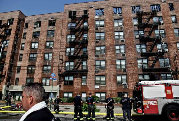 Firefighters recoil a hose outside an apartment building after putting down a fire that engulfed its upper floors in the Brooklyn Borough of New York, Thursday, July 26, 2012.  The blaze injured dozens of firefighters and forced the evacuation of more than 100 families to a temporary Red Cross shelter. (AP Photo/Bebeto Matthews) Photo: Bebeto Matthews