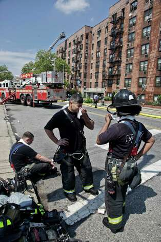 Firefighters rest outside an apartment building after putting down a fire that engulfed its upper floors in the Brooklyn Borough of New York, Thursday, July 26, 2012. The blaze injured dozens of firefighters and forced the evacuation of more than 100 families to a temporary Red Cross shelter. (AP Photo/Bebeto Matthews) Photo: Bebeto Matthews