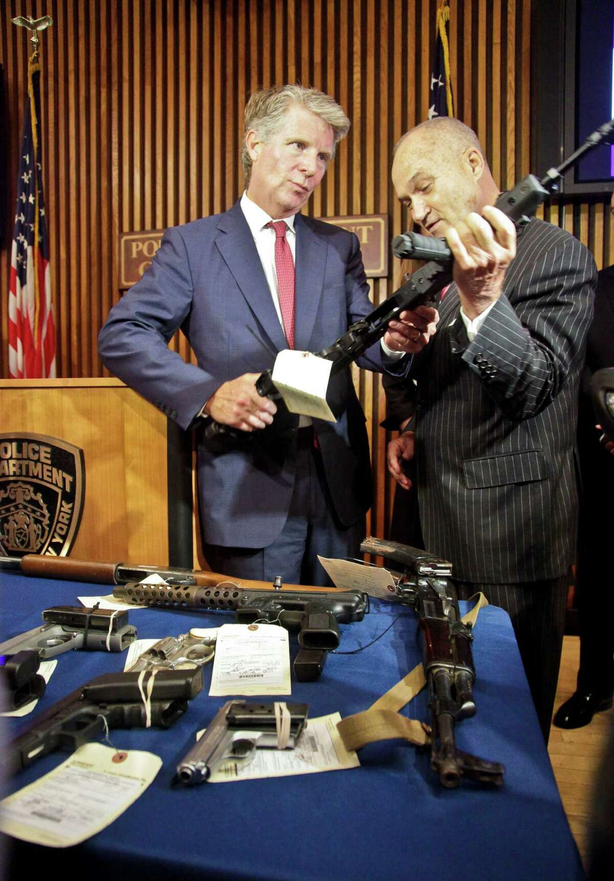 New York Police Department Commissioner Raymond Kelly, right, and Manhattan District Attorney Cyrus Vance, Jr., looks over a firearm at a press conference after announcing the indictment of 33 defendants for stealing and selling motorcycles and illegal firearms, Thursday, July 26, 2012 in New York. (AP Photo/Bebeto Matthews)
