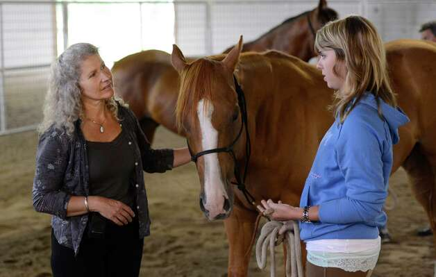 Military suicide widow Rebecca Morrison, right speaks with Saratoga War Horse instructor Melody Squier during her introduction to the Saratoga War Horse Program in Saratoga Springs, N.Y. July 26, 2012    (Skip Dickstein/Times Union) Photo: Skip Dickstein