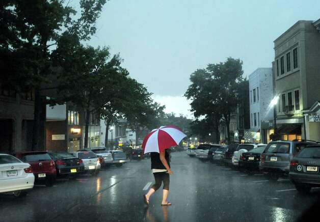 A woman with an umbrella crosses Greenwich Avenue during the storm that passed through the area Thursday night, July 26, 2012. Photo: Bob Luckey / Greenwich Time