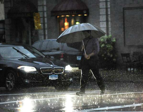A man with an umbrella heads north on Greeenwich Avenue during the storm that passed through the area Thursday night, July 26, 2012. Photo: Bob Luckey / Greenwich Time