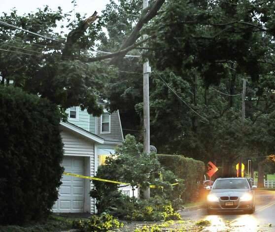 Tree limbs rest on utility lines as a car passes near downed tree limbs on East Elm Street during the storm that passed through the Greenwich area Thursday night, July 26, 2012. Photo: Bob Luckey / Greenwich Time