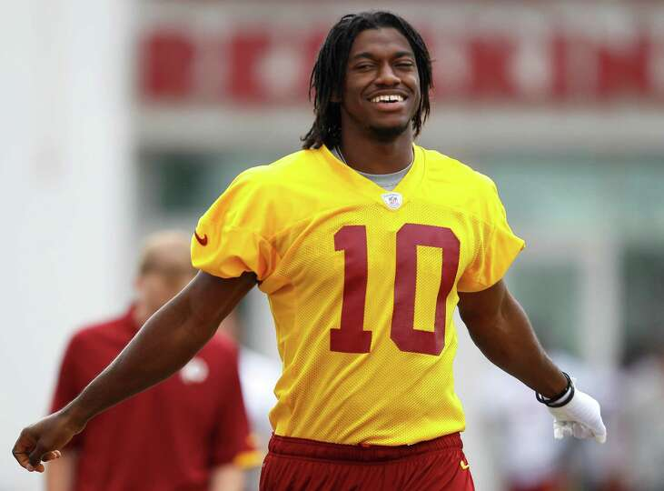 Washington Redskins quarterback Robert Griffin III walks to a morning practice at NFL football train