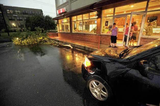 Witnesses at Dubl Twister ice cream shop on White Street in Danbury say lightning struck a tree and fell on the car at right during a thunderstorm that went through the area Thursday, July 26, 2012. Photo: Jason Rearick / The News-Times