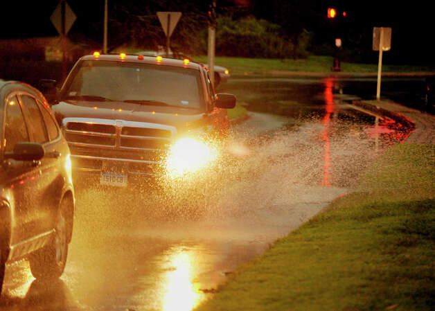 Vehicles navigate the large puddles of water on Patriot Drive in Danbury as a thunderstorm hits the area Thursday, July 26, 2012. Photo: Jason Rearick / The News-Times