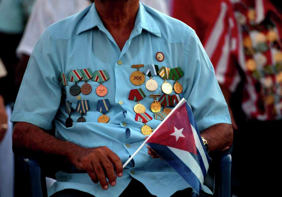 A veteran of the Revolution wears his military medals and holds a Cuban flag at an event celebrating Revolution Day in Guantanamo, Cuba, Thursday, July 26, 2012. Cuba marks the 59th anniversary of the July 26, 1953 rebel attack led by Fidel and Raul Castro on the Moncada military barracks. The attack is considered the beginning of the revolution that culminated with dictator Fulgencio Batista's ouster. (AP Photo/Ramon Espinosa) Photo: Ramon Espinosa / AP