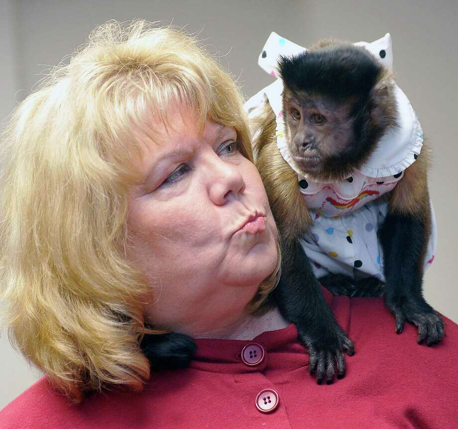 Debbie Berg seeks a kiss from Keko, her black cap Capuchin monkey, after Judge Tom Rugg ruled that she can ignore a Mississippi woman's lawsuit. Photo: Dave Ryan