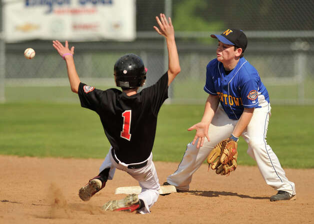 New Canaan's Jim Stanley slides safely into second after an errant throw to Newtown shortstop Lucas O'Brien during their Cal Ripken 12-year-olds New England tournament final at Glander Field in Newtown on Thursday, July 26, 2012. New Canaan won 9-8 in 11 innings. Photo: Jason Rearick / The News-Times