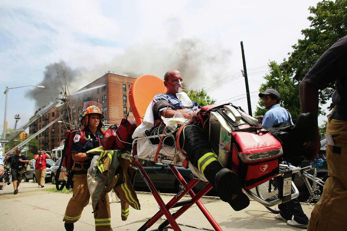 NEW YORK, NY - JULY 26: A New York City firefighter is taken away on a stretcher from the scene of a six-alarm fire at a seven-story apartment building in the Prospect Lefferts Gardens of Brooklyn on July 26, 2012 in New York City. Fire officials have reported 14 injuries among residents and firefighters at the building, which houses 115 residential units. (Photo by Spencer Platt/Getty Images)