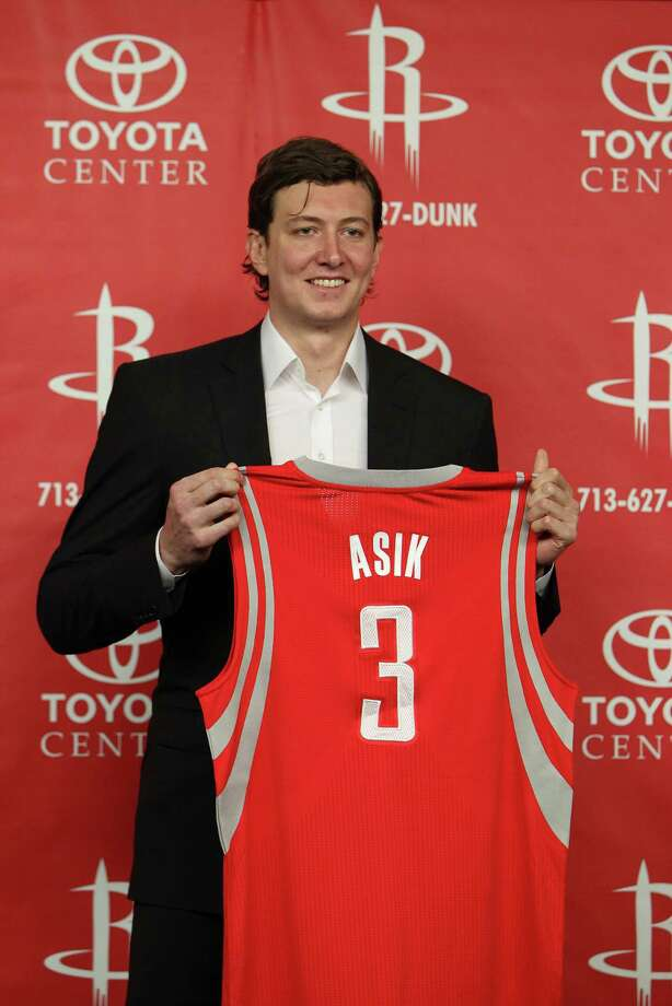 Omer Asik holds up his new Houston Rockets jersey as he was introduced during a Rockets press conference at Toyota Center, Thursday, July 26, 2012, in Houston.  ( Karen Warren / Houston Chronicle ) Photo: Karen Warren / © 2012  Houston Chronicle