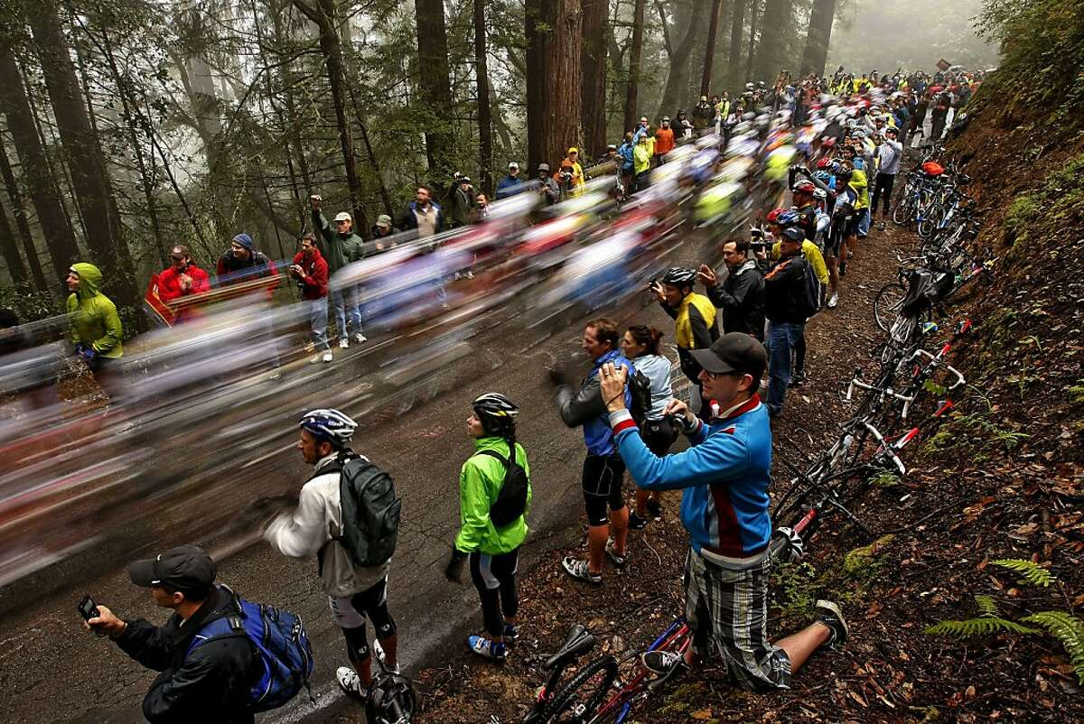 Waldo Williams, of San Francisco, (bottom center) photographs the peleton as it up zooms up Tunitas Creek Road past crowds of fans near Skyline Blvd. under foggy and misty skies, as stage 3 is underway in the 2010 Amgen Tour of California bicycle race featuring the world's best riders on Tuesday May 18, 2010, in San Francisco, Calif.