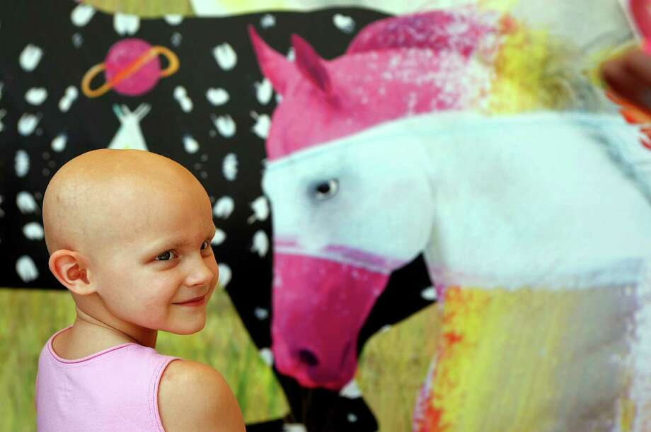 "Julia Cobb, 7, smiles after looking at the digital art mural of 25 horses that was unveiled that was created by herself and about 75 other patients and siblings titled ""Light, Hope, Wonder"" outside the MD Anderson Children's Cancer Hospital in the Texas Medical Center Thursday, July 26, 2012, in Houston. The mural was organized and run through the Arts in Medicine Program at MD Anderson Children's Cancer Hospital. Photo: Johnny Hanson, Houston Chronicle / © 2012  Houston Chronicle"