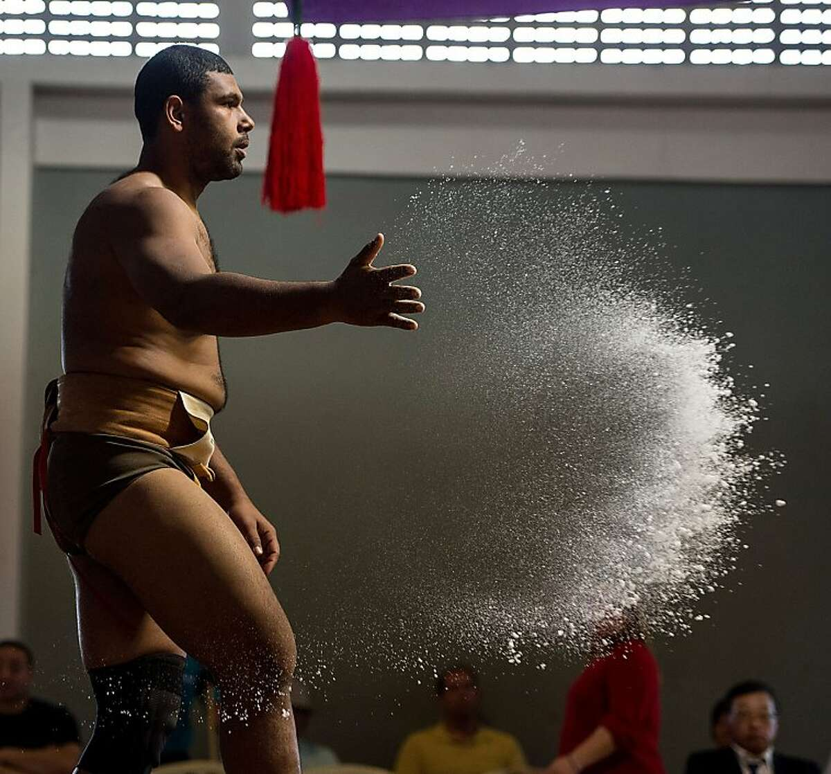 Cassio Gomes of Brazil throws a handful of salt into the ring during the Sumo wrestling South American Championship in Sao Paulo, Brazil, on July 22, 2012. AFP PHOTO/Yasuyoshi CHIBAYASUYOSHI CHIBA/AFP/GettyImages